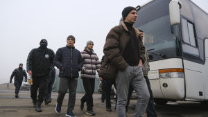 Fångar gick mot sina bussar vid Majorsk på söndagen. De flesta var inte bekymrade över att bli identifierade, men en del av dem täckte sina ansikten.