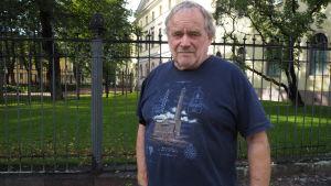 äldre man i blå t-skjorta står framför ett järnstaket vid gult stenhus och park i Åbo.