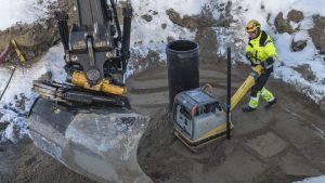Työmies tiivistää hiekkaa putken ympäriltä.