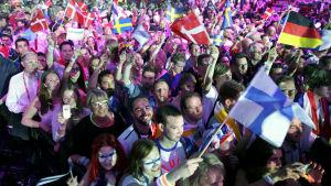 Eri maiden euroviisufaneja kasvomaaleissa ja lippuja liehuttamassa yleisössä.