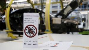 Bild på skylt med coronavirusbild, i bakgrunden tillverkas en bil.