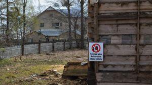 Skylt som varnar för byggarbete vid tomt med gammalt hus.