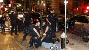 Poliser griper en demonstrant som ligger på marken