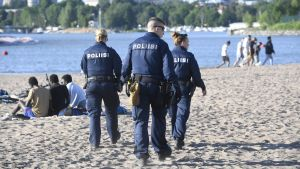 Tre poliser går på Sandudds badstrand.