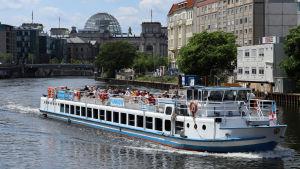En båt med turister på sightseeing på floden Spree i Berlin