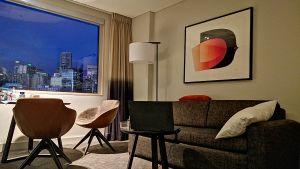 Ett hotellrum i skymning med tre stolar, en grå soffa och en tavla.