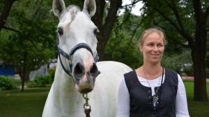 Kvinna med ljust hår står på gräsmatta tillsammans med vit häst.