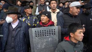 En grupp män står på en trappa. En av dem är utrustad med en kravallsköld