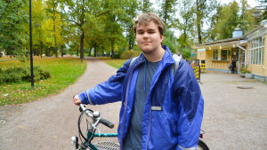 En ung man med sin cykel.