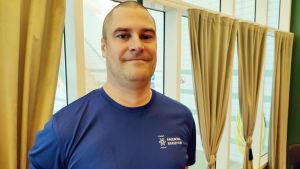 En man med rakat huvud och blå t-skjorta. I bakgrunden stora fönster där man kan se bassängerna i Ekenäs simhall.
