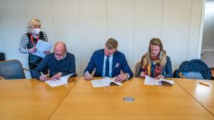 Tre personer sitter vid bord och skriver på papper, en kvinna med munskydd står bredvid