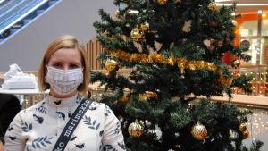 Kvinna med ljust halvlångt hår står framför julgran i köpcenter. Kvinnan bär ett ljust ansiktsskydd.