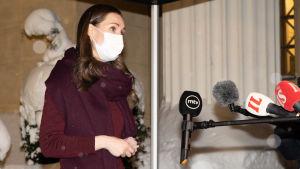 Sanna Marin med munskydd framför mikrofoner på Ständerhusets snöiga trappa.