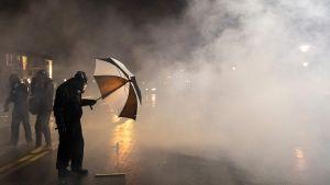 En demonstrant utanför polisstationen i Brooklyn Center skyddar sig mot polisens tårgas sent på måndag kväll, lokal tid.
