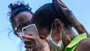Allison Haywood kramar sin gråtande mamma Cheryl Haywood utanför en kyrka i Washington DC efter domen i Minneapolis.