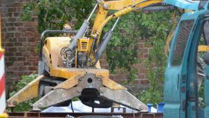 En gul rivningsrobot som är fastsvetsad i en stålram. Till utseendet påminner maskinen lite om en grävmaskin, med en robotiserad arm. Maskinen saknar dock förarsäte.
