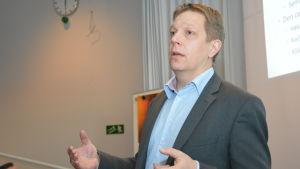 Konsult Marcus Henricson presenterar rapporten om skolnätsreformen i Raseborg på ett invånarmöte.