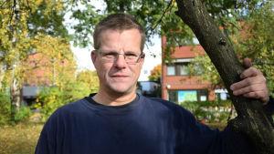 Postutdelaren Thomas Hansson står vid ett äppelträd. I bakgrunden syns träd med gula löv.
