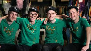 Kevin Holmström, Christoffer Strandberg, Axel Åhman och Jakob Norrgård sitter och håller varandra om axlarna. Alla är iklädda gröna t-skjortor och svarta kepsar.