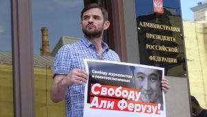 En man som demonstrerar håller upp ett plakat med Ali Feruz bild