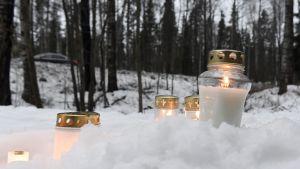 Flera ljus har placerats i snön vi Karabacka där en död 13-åring försvann.