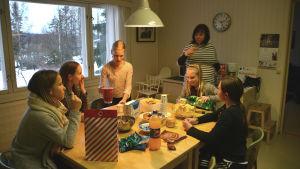 Flera flickor sitter runt ett bord med godsaker. I bakgrunden står en kvinna.