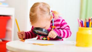 Ett barn tittar på ett papper genom ett förstoringsglas.