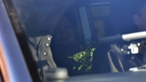 Jenni Haukio inne i bilen med blombukett.