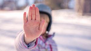 Flicka sätter ut handen som ett stoppmärke.
