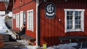 Kvinna med hund solar sig vid café Måsen i Hammars.