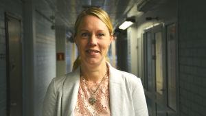 johanna bonäs står i en lång ganska mörk korridor. hon bär en vit blus och kavaj.