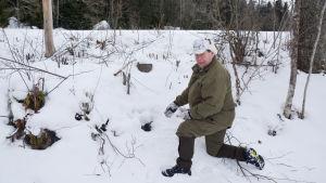 Christian linden i en snöig slänt pekar på ett litet hål i marken
