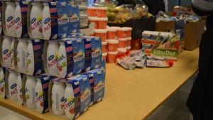 En rad med jogurtburkar och annan mat står uppradade på ett bord.