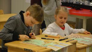 En pojke och en flicka sitter vid sin pulpet och ritar myror i en myrstack.