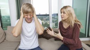 En man håller händerna för öronen medan en flicka försöker förklara något.