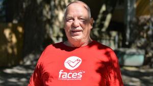 En man i röd t-skjorta som har en bild på vit duva och texten faces. Det är Börje Mattsson.