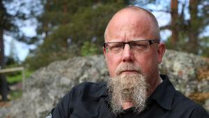 En medelålders man med långt skägg och glasögon sitter på en bänk.