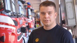 aatu isotalo står i räddningsverkets garage. han bär arbetskläder och i bakgrunden figurerar en rad av brandbilar.