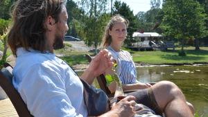 Patrik och Cecilia Laine sitter på en terass vid havet och pratar.