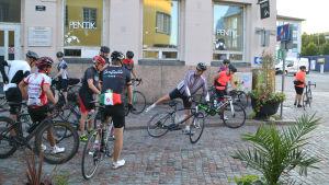 Flera cyklister står på Krämaregatan i Borgå och gör sig redo. En man i mitten svingar sig upp i cykelsadeln.