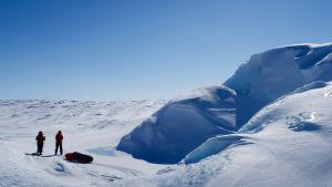 Två personer står i ett snölandskap. De befinner sig på Grönland. De skidar och har pulkor efter sig. Till höger om dem syns ett stort snöberg.