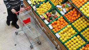 En kund står vid en grönsaksdisk i en livsmedelsaffär.