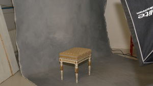 En stol står vid en grå bakgrundsvägg, färdig för fotografering.