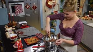Nainen sulattaa suklaata vesihauteessa.