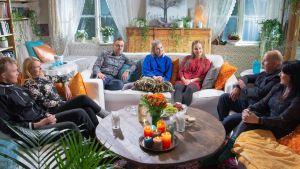 Pöydällä on oransseja kukkia ja sinisiä sekä oransseja kynttilöitä. Kuva on laaja kuva Timosta ja hänen läheisistään, jotka ovat Tuhkimotarinoiden ohjaaja Mape Morottajan vieraana.