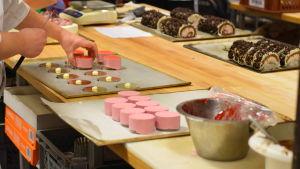 Runda ljusröda bakelser dekoreras med röd gelé. I bakgrunde choklad och gräddbakelser.