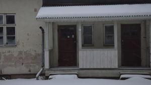 Ett vitrappat hus  där rappningen delvis fallit bort och ett stuprör hänger också löst. Vinter och snö. Huset är obebott.