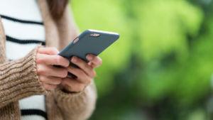 Flicka skriver på mobiltelefon