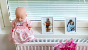 Ikkunalaudalla vauvanukke ja kaksi valokuvaa Nadja-äidistä lasten kanssa.