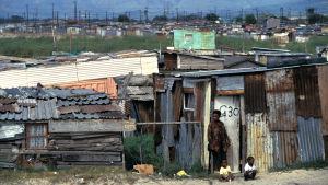 Slum i Kapstaden. Ruckel och pojke samt två små barn smått i ena hörnet.